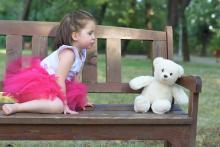 Mädchen betrachtet einen Teddybären auf einer Bank